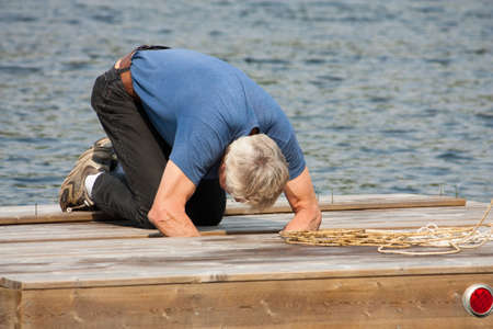 A senior man bent over working on repairs on an aging wooden dock or raft with the lake in the background 版權商用圖片
