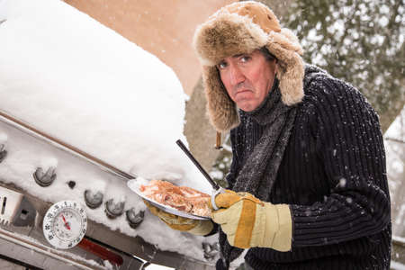 Snow continues to fall on a middle aged man as he goes to light his barbeque only to find it covered in snow in the sub zero temperatures  photo