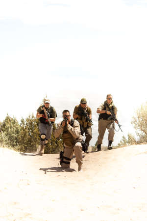semi automatic: A special forces military team runs a tactical formation in a desert operation Stock Photo