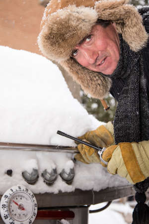 griller: This unhappy griller looks as though he would rather be heading south for a winter vacation than starting his BBQ in the snow