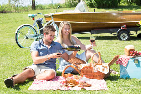 A couple enjoys a summer picnic by the lake in a country setting photo