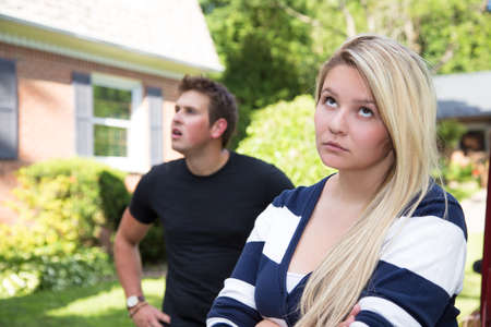disagreeing: A young couple having a disagreement.  The young lady rolls her eyes at the young man who seems distracted and confused in the background. Stock Photo