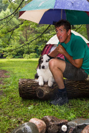 soggy: A soggy camper with his dog huddles under an umbrella anxiously waiting for the rain to stop