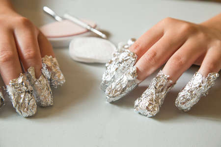waiting for the shellac to soften.  The nails are applied with acetone and wrapped in aluminum foil to remove shellac nails saefly at home Stock fotó - 30121135