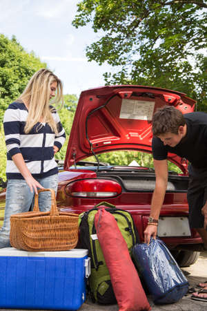 A young couple packs their trunk for a camping trip