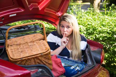 A young woman hides in the trunk of a car that has been loaded with items in preparation for a summer trip photo