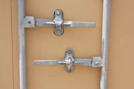 The door of a metal sea crate storage, close up on the locking system
