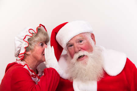 Mrs Claus whispers a secret into Santas ear.  Perhaps she knows who has been naughty or nice. Stock Photo