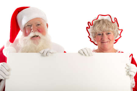 A laughing Santa and Mrs Claus hold up a white sign with lots of space for your message.