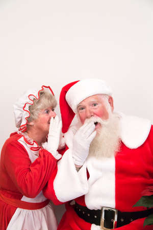 Mrs Claus whispers a secret into Santa