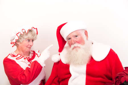 A sad and grumpy Santa being scolded by Mrs Claus. Stock Photo