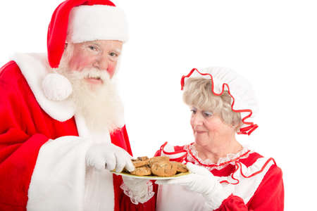 Mrs Clause offers Santa cookies from a plate