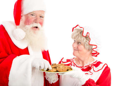 A laughing Santa takes a cookie from the plate Mrs Clause offers him.