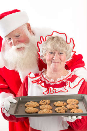 Mrs Claus beams while holding a tray of cookies on a tray, fresh from the oven.  Santa looks excitedly over her shoulder at the fresh warm cookies