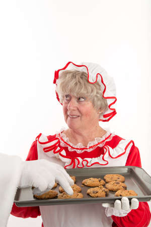 Mrs Claus looks up at Santa who is outside the frame as Santas gloved hand is seen reaching in to get a cookie from her tray.