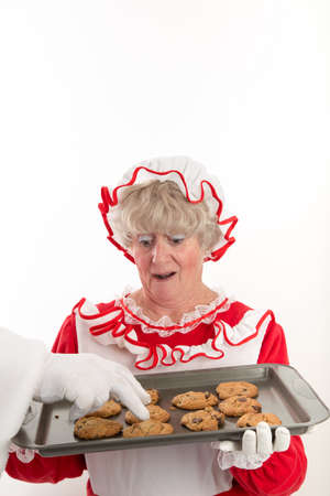 A white gloved hand of Santa reaches into the frame to steal a cookie from the tray of a startled Mrs Claus is holding