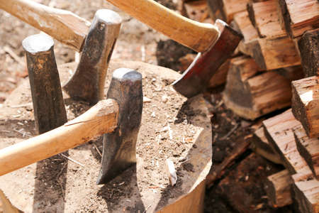 splitting up: A large block of wood holds several axes for wood splitting during spring clean up weekend at the cottage
