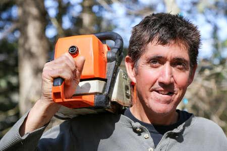 long weekend: Un uomo con una motosega a tracolla prende una pausa dal cantiere clean-up al cottage.