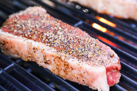 A perfect 1 inch thick New York strip loin steak, seasoned and grilling over the flame on the barbecue