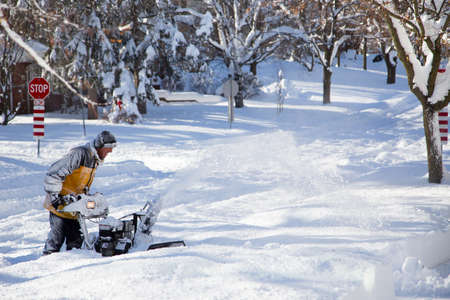 A thick layer of snow covers the road as a man with a snow blower tries to find his walkway to clear
