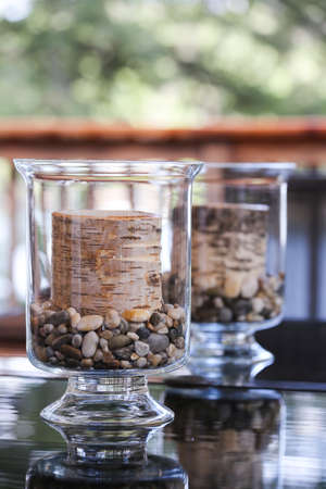 muskoka: Birch tree candles in glass holders adorn the outdoor table at the cottage.  Perfect Muskoka decor.