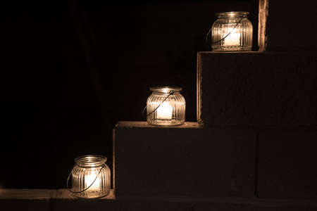 tiered: Three jar lights on a tiered cement wall steps on black of darkness Stock Photo