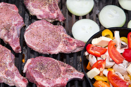 pork chops: Nice thick pork chops on the grill with onions and an iron skillet of vegetables on the side