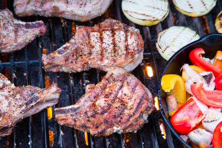 pork chops: Pork chops sizzling over the flames of a summer grill