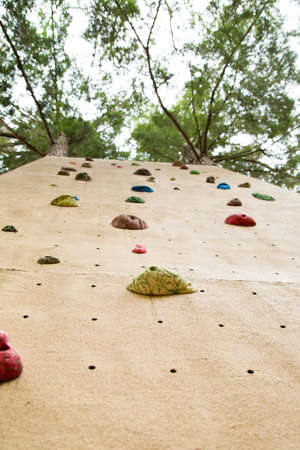 facing a wall: view from the ground looking up at an outdoor climbing wall.  Implies concept of facing challenge and heading upwards