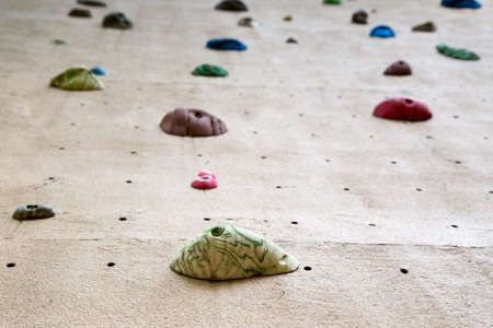 shallow depth of field looking up a climbing wall focused on the foot grip closest to the camera Stock Photo