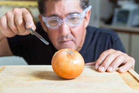 A man in the kitchen tries to cut an onion using goggles to avoid tears Standard-Bild