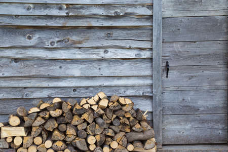 woodshed: a pile of slit firewood sits piled beside a rustic woodshed