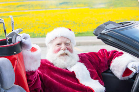 Santa Claus driving a convertible with golf clubs