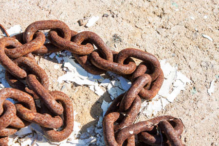 unbreakable: heavy gauge marine chain rests rusting on the shore in the hot sun
