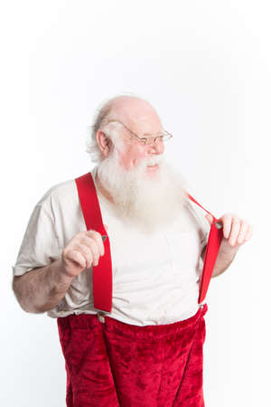 jovial: A laughing Santa Claus in under shirt and red suspenders as he dresses for Christmas eve