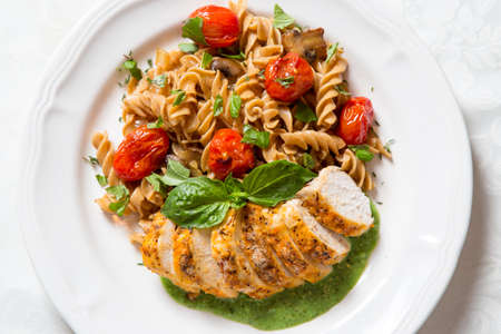 A delicious chicken and whole grain pasta dinner on a white plate with fresh basil. Shot from overhead view.