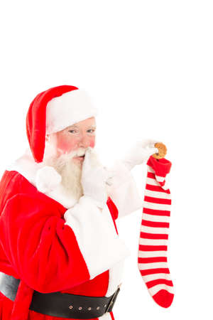 shush: Santa putting a cookie into a Christmas stocking, on a white background