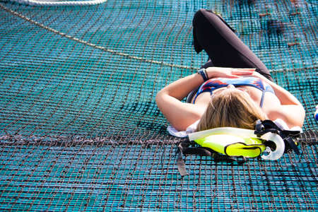 Lounging in the sun on the net of a catamaran on a cruise ship excursion in the Caribbean