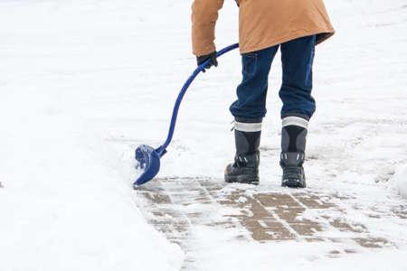 Un uomo con una curva sgombero neve neve pala gestita da un marciapiede del mattone in inverno canadese.