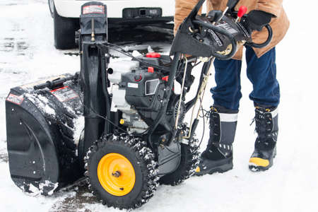 waist down: A man shown from the waist down, starting up his snow blower in the winter Stock Photo