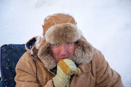 winter weather: A man in the snowy winter weather bundled up to protect himself against the cold Stock Photo