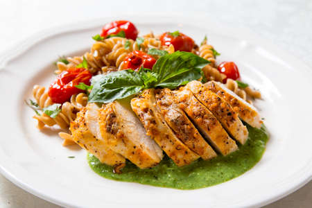 plating: colorful and healthy chicken dinner with whole wheat pasta Stock Photo