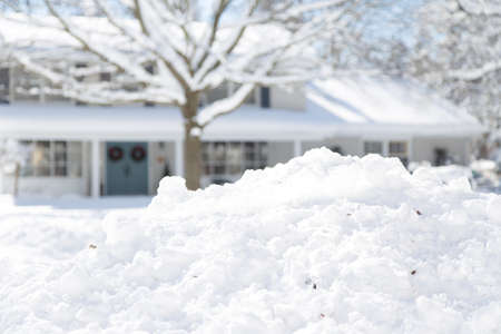 heap of snow: shallow depth of field focused on snow with the house in background Stock Photo