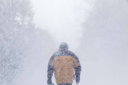 a man with his back to the camera, walking away through a heavy snow storm Standard-Bild