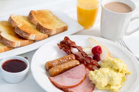 Un delicioso desayuno americano tradicional de tocino, salchicha, jamón y huevos revueltos con todos los adornos en un bonito mantel blanco brillante Foto de archivo