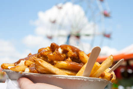 cuisine entertainment: Poutine, a Canadian favorite at the fair, where junk food reigns supreme, held up in front of the ferris wheel