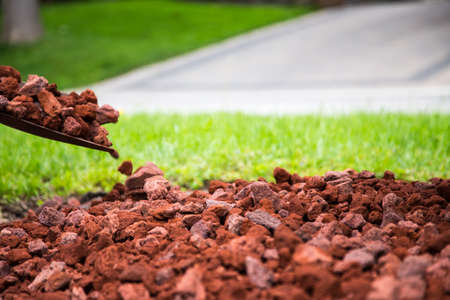 making a new garden with red lava rock. shallow depth of field on the lava stone at the thirds line leaves soft focused background for copy.