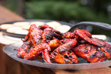 plate of BBQ chicken wings in summer on the deck at the cottage