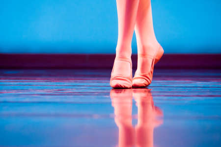 zapatillas ballet: A los pies de los bailarines en zapatillas de ballet que reflejan también en el escenario azul brillante vibrante