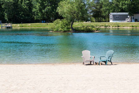 two empty Muskoka chairs set on the beach by some sandcastles in front of a pond Stock Photo